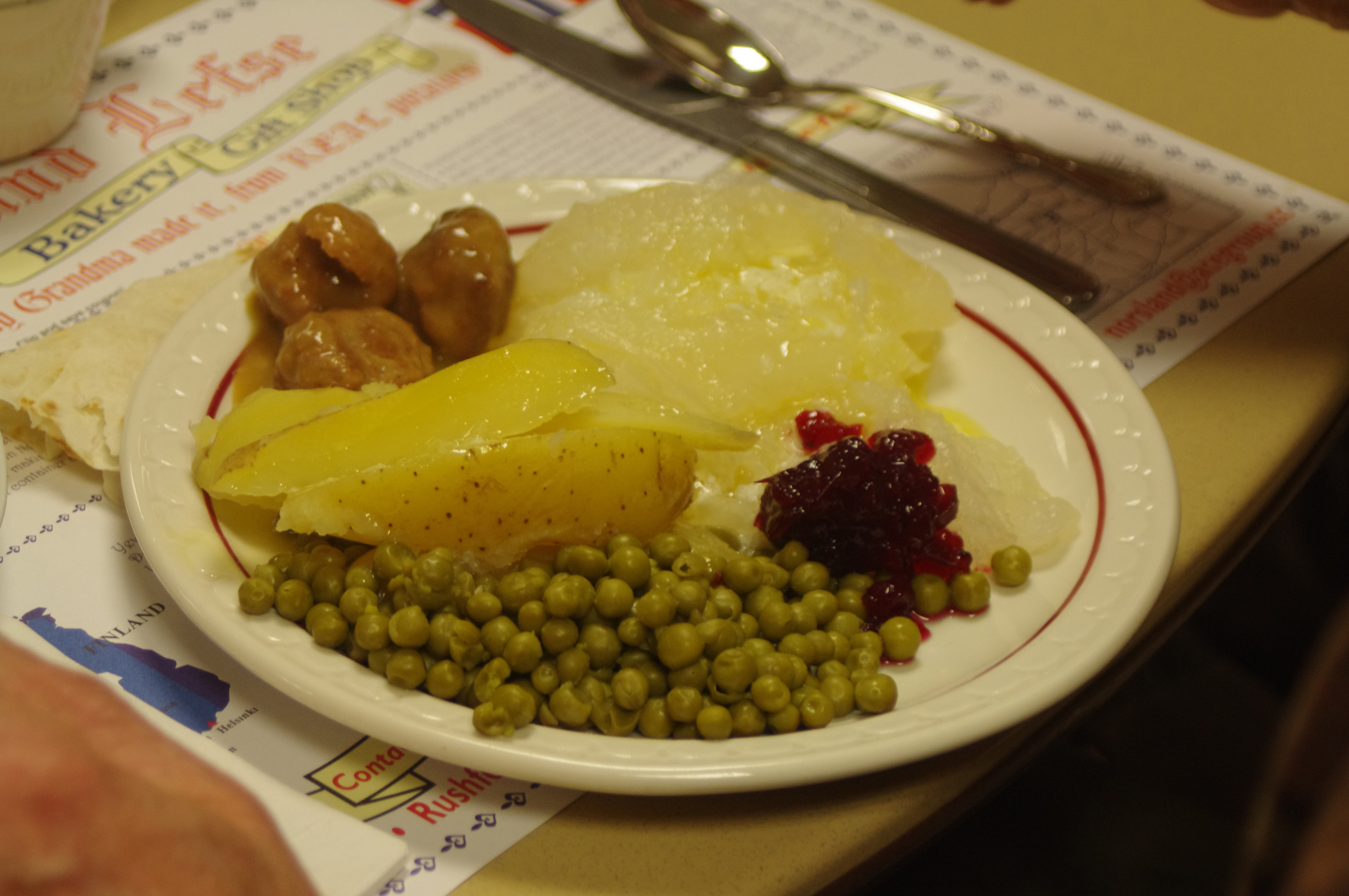 Image of meatballs, lutefisk, cranberry relish, peas and potatoes on a plate
